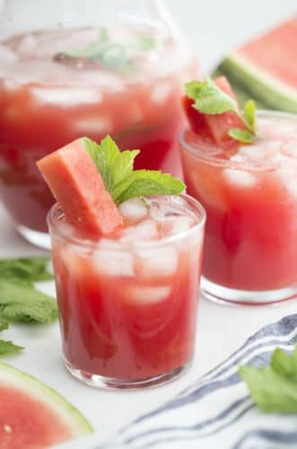 A couple glasses of watermelon agua fresca with a stick of watermelon and fresh mint.