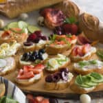 A group of canapés on a wooden board topped with various ingredients