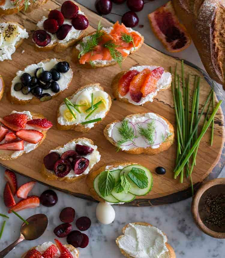 Canapés topped with fresh fruits, vegetables, smoked salmon and quails eggs.