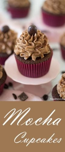 Chocolate cupcake with chocolate covered coffee bean on top sitting on a cupcake stand.