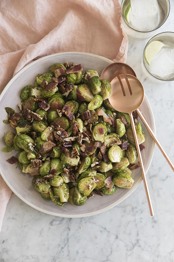 A photo of Brussel sprouts with bacon and caramelized pecans on a serving dish.
