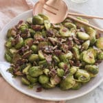 A photo of Brussel sprouts on a serving dish with crispy bacon and caramelized pecans.