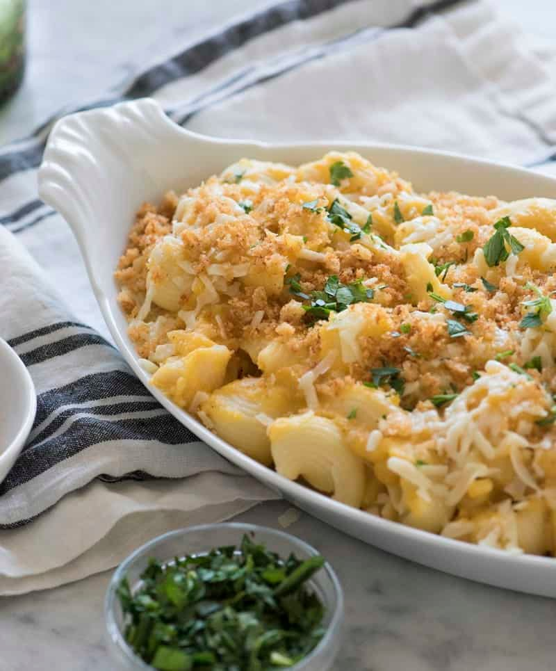 photo of mac and cheese ina serving dish. topped with a sprinkle of toasted breadcrumbs and parsley