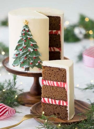 A photo of a gingerbread cake with a painted Christmas tree made from butter cream on the front.