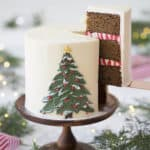 A photo of a gingerbread cake with a painted buttercream pine tree on the front and a piece being removed.
