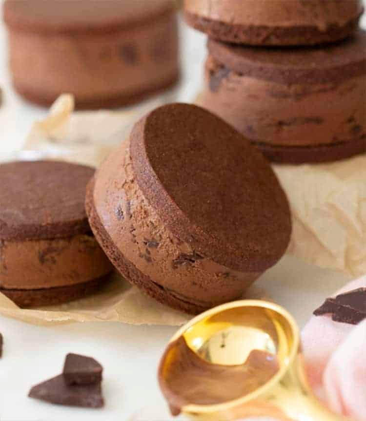 chocolate ice cream sandwiches with a brass scooper in the foreground