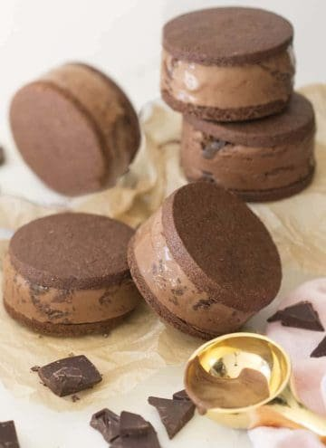 Chocolate ice cream sandwiches with a gold scooper in the foreground