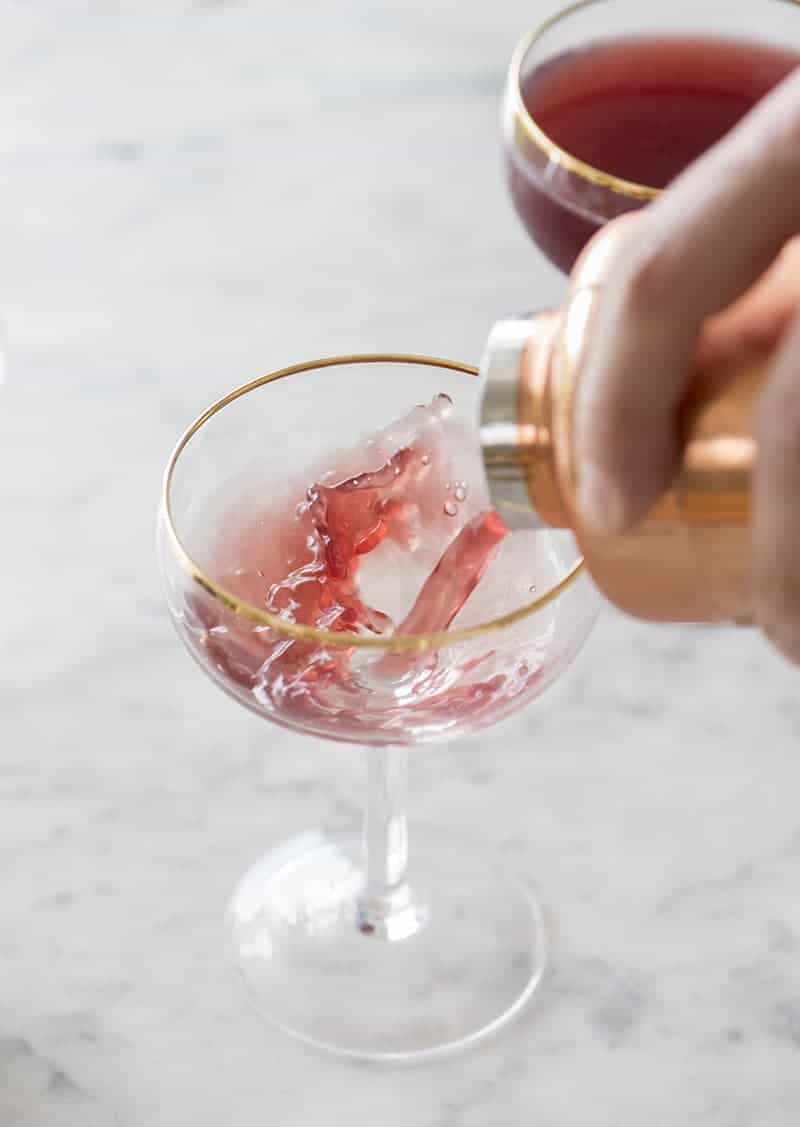 photo of a Pomegranate martini being poured into a coupe glass