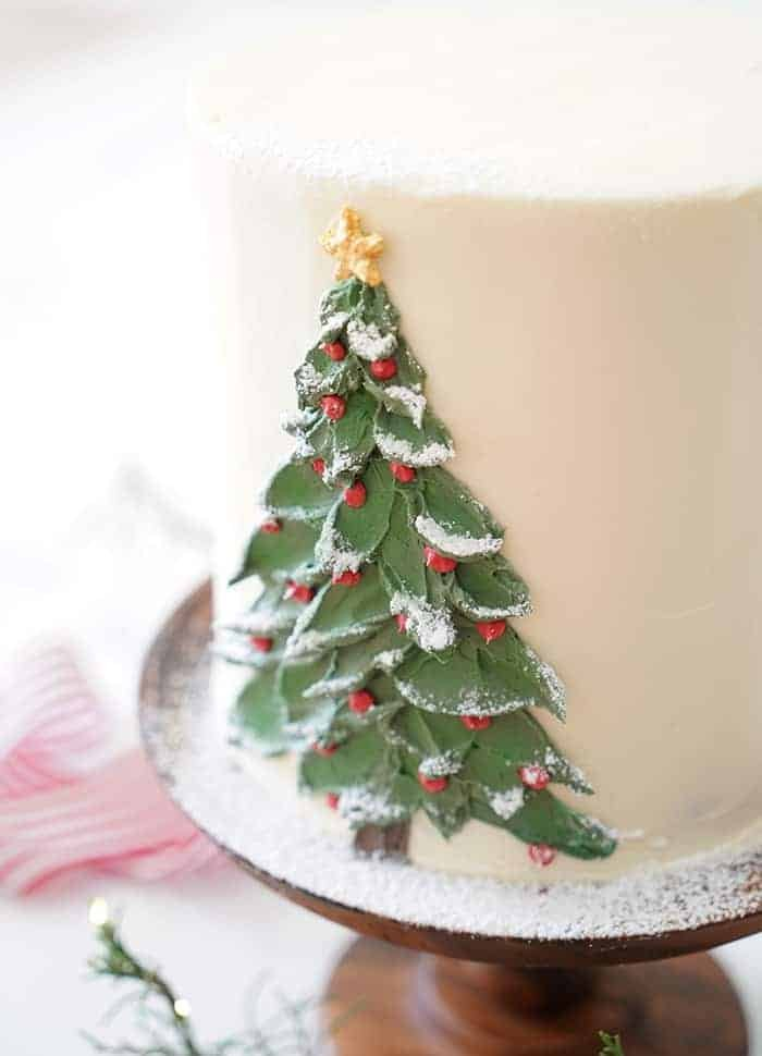 A close up photo of a buttercream Christmas tree painted onto a cake