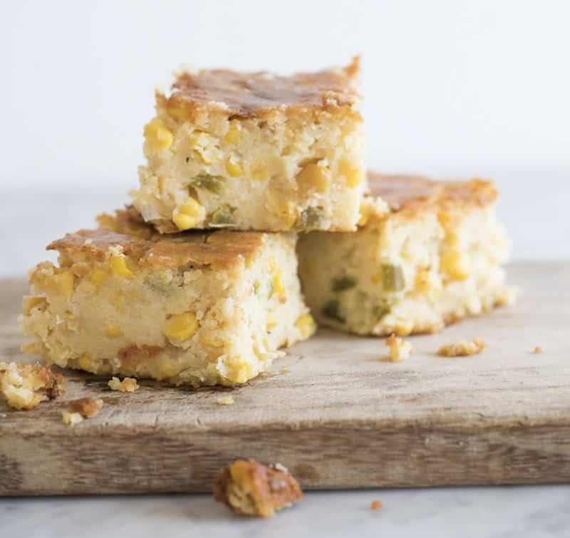photo of a cornbread pudding squares on a wooden board