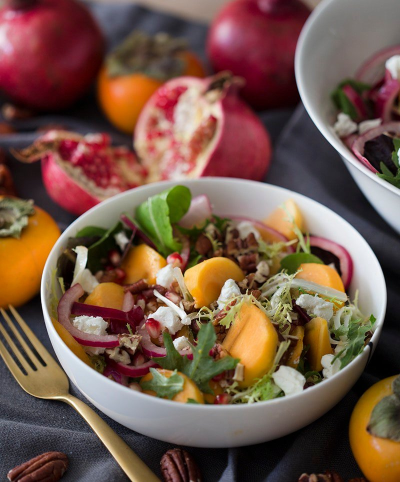 Photo of a persimmon sapad arranged in a bowl surrounded by pomegranates and persimmons
