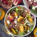 Photo of a persimmon salad with pomegranate seeds and pecans in a white bowl