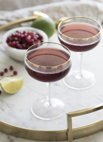 Photos of pomegranate martinis in coupe glasses on a tray