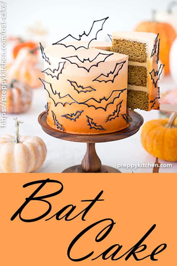 A clipping of a cake with bats all over it, on a wooden cake stand with pumpkins around it.