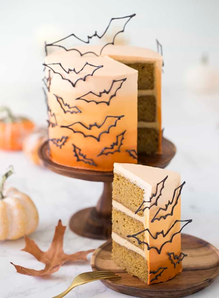 photo of an ombre orange cake covered in candy melt bats on a wooden cake stand with a piece in the foreground