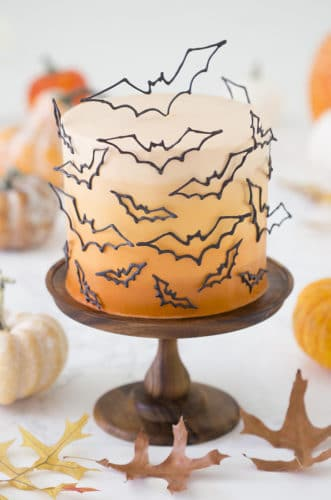 photo of an ombre orange cake covered in candy melt bats on a wooden cake stand