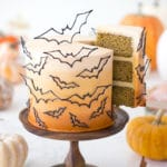 photo of a n ombre orange cake covered in candy melt bats with a piece being removed.