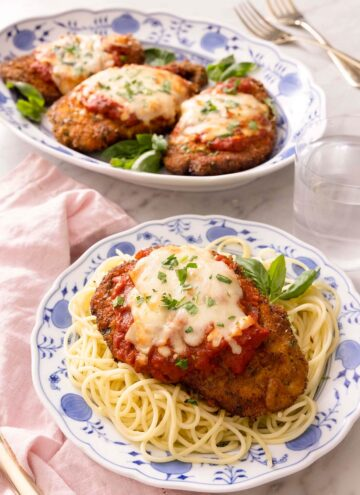 Chicken parmesan on a blue plate with spaghetti