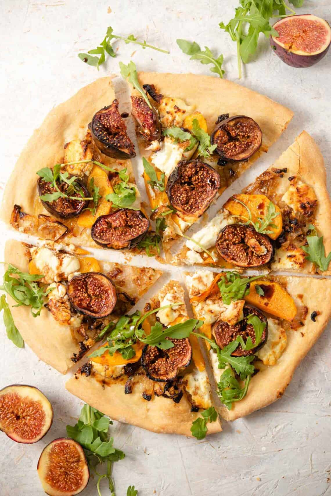 An overhead shot of a fig pizza cut into slices