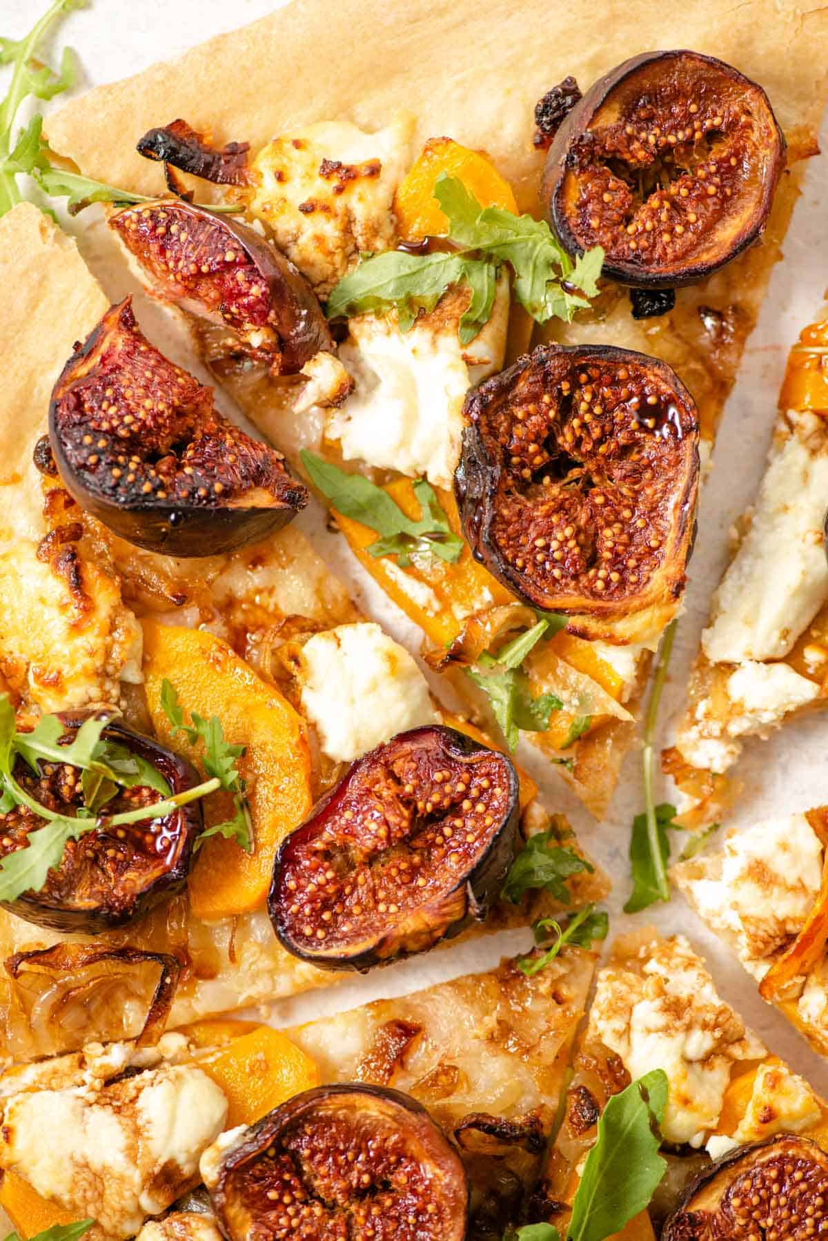 A close up of slices of pizza topped with figs and goats cheese