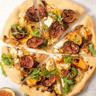 A close up of a fig pizza cut into slices