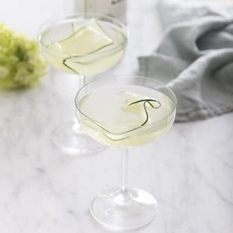A photo of a cucumber martini in a coup glass on a white marble table