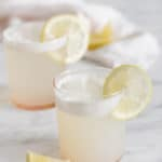 Photo of two gin fizz cocktails on a white marble table