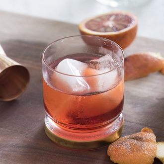 A photo of a blood orange negroni with a flamed peel next to it.