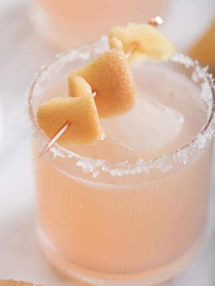 A close up photo of a paloma cocktail rimmed with salt