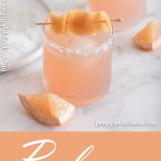 A clipping of a Paloma cocktail with sliced grapefruit laying next to it.