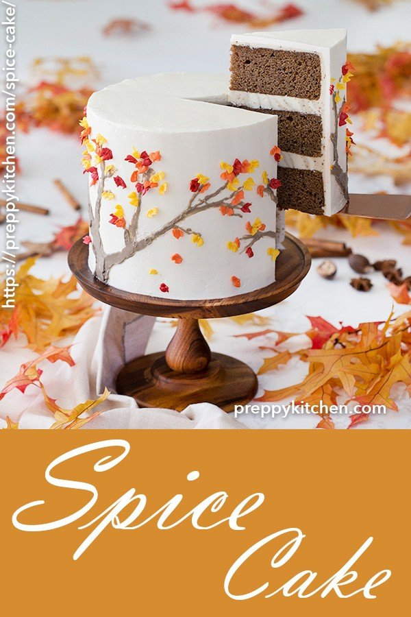 A clipping of a spice cake on a cake stand, with a piece being removed.