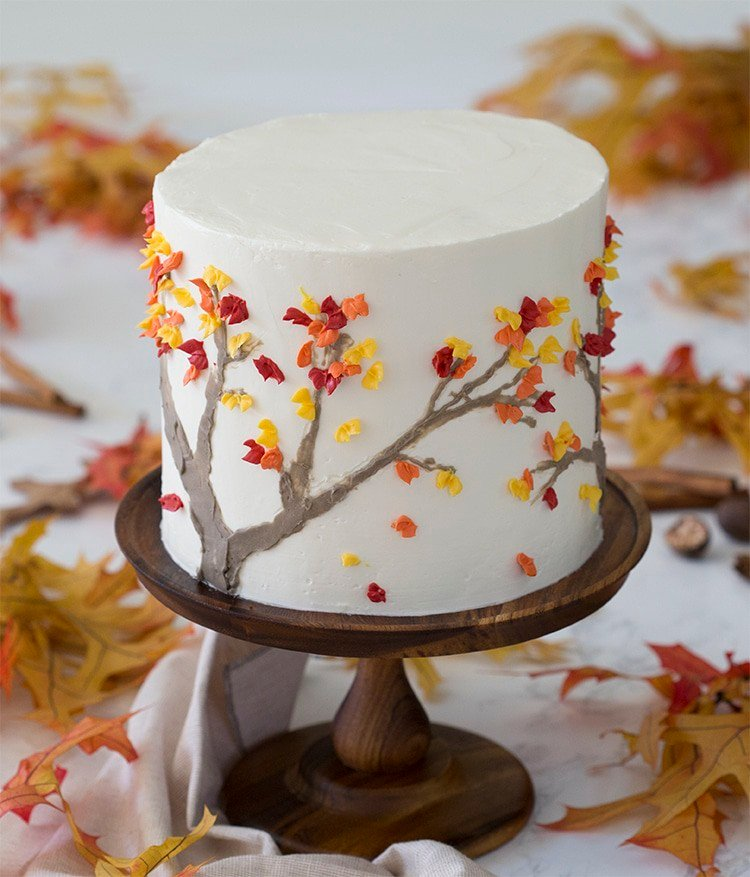 a photo of a spice cake on a wooden cake stand surrounded by fall leaves.