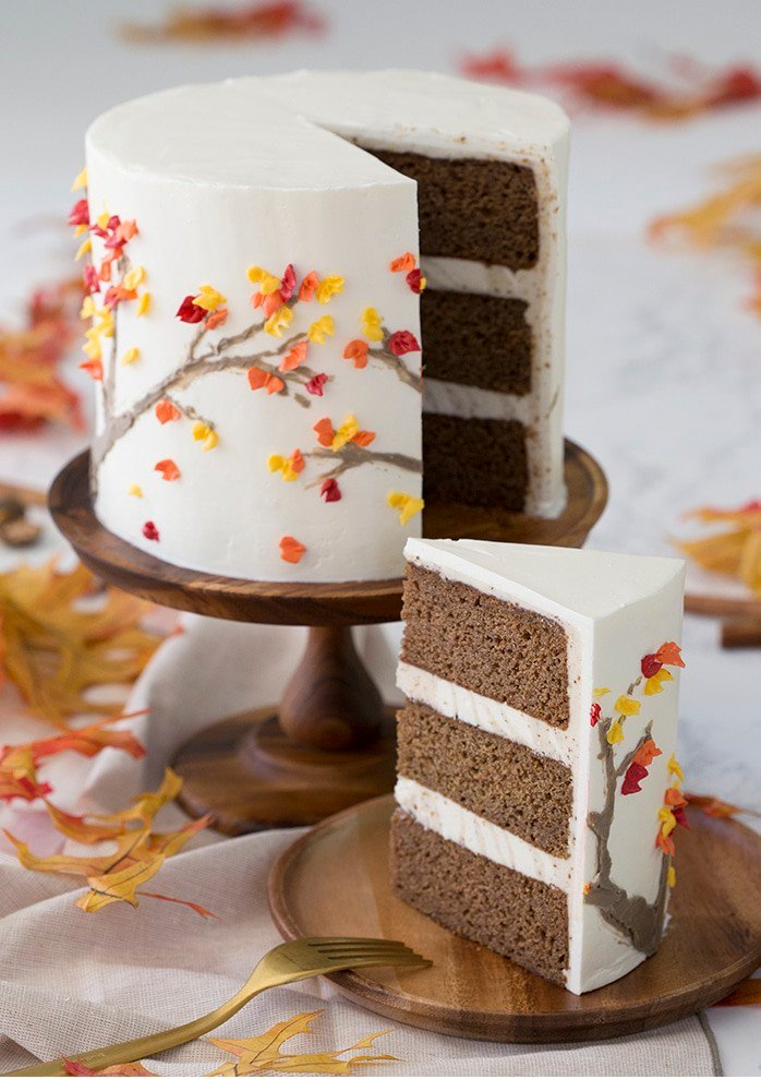 Photo of a spice cake on a wooden cak stand. A piece is removed and on a wooden plate in the foreground.
