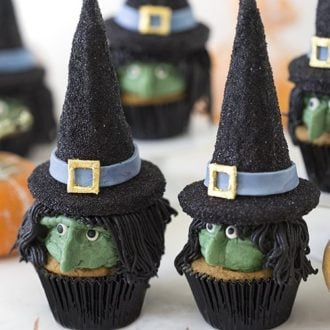 a photo with two Witch cupcakes in the foreground