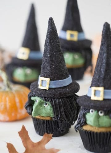 A photo of realistic looking witch cupcakes on a white table
