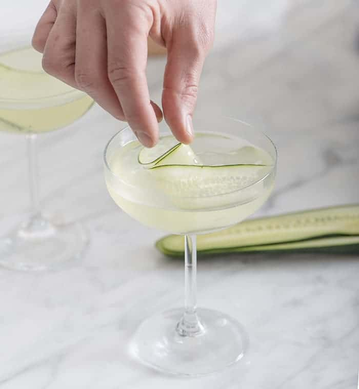 A photo of a cucumber martini being garnished
