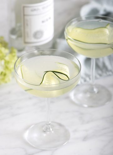 A photo of two cucumber martinis on a white marble table garnished with a thin cucumber slice.