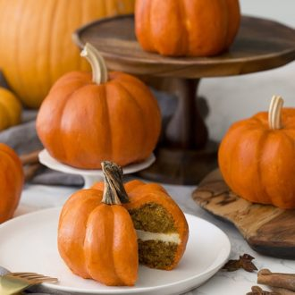 mini pumpkin cakes on a table with real pumpkins mixed in.