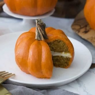 A pumpkin Bundt cake that looks just like a pumpkin with a piece cut out showing the cake inside