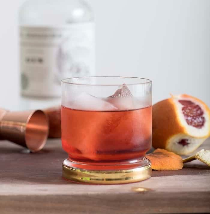 A photo of a negroni cocktail on a wooden cutting board