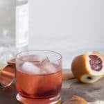 A photo of a negroni with a flamed peel next to it