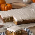 A pumpkin poke cake covered in brown butter frosting with a pice in the foreground.