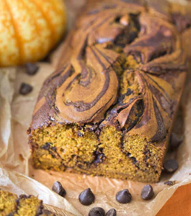 A load of chocolate swirled pumpkin bread on an orange linen.