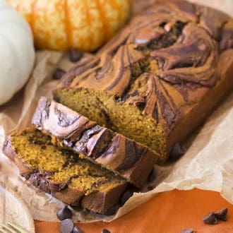 A load of pumpkin bread swirled with chocolate that has had two pieces cut from it.