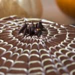 A chocolate spider sits on a chocolate spider web covered sheet cake