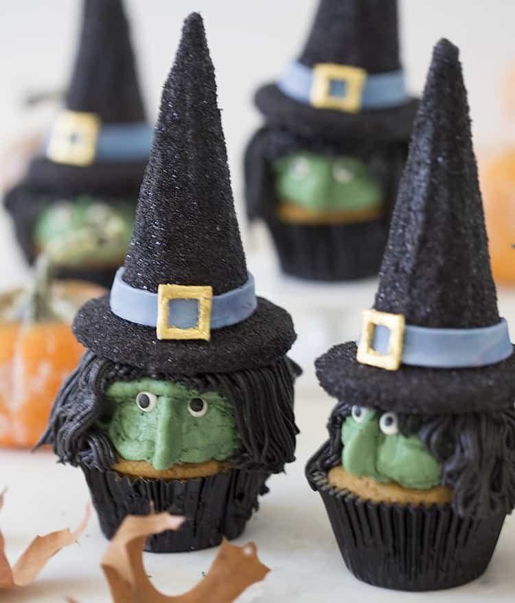 A photo showing a group of Witch hat cupcakes with green faces and black hair