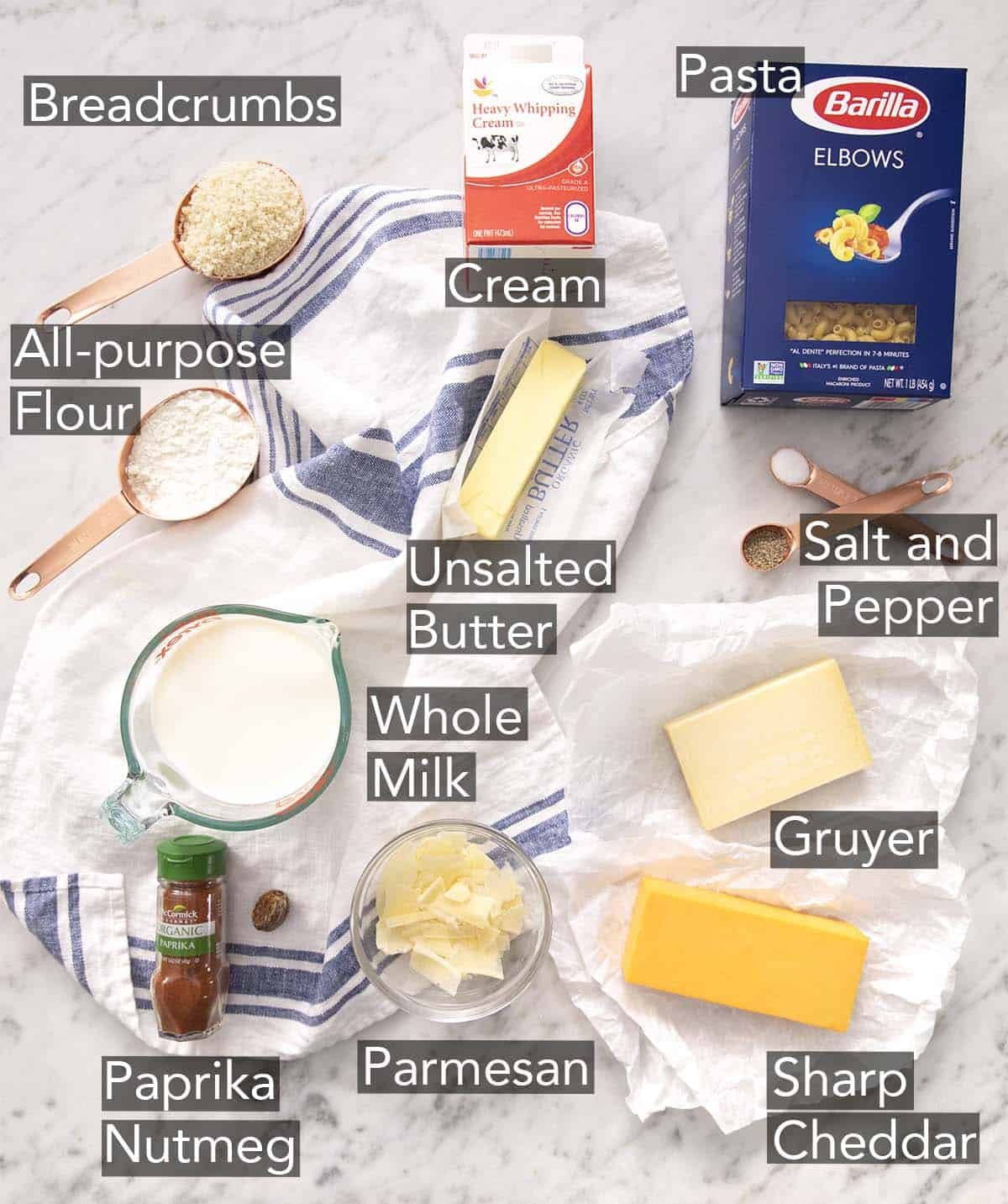 Ingredients to make baked mac and cheese on a marble counter.