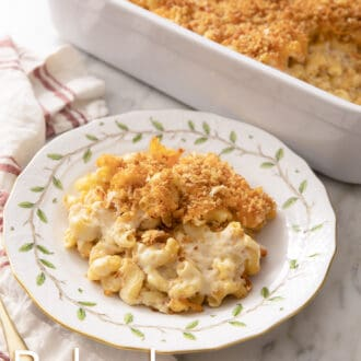 Baked mac and cheese with toasted breadcrumbs on a plate with painted leaves.