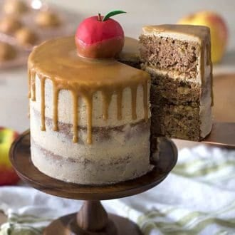 A caramel apple cake on a wooden cake stand.