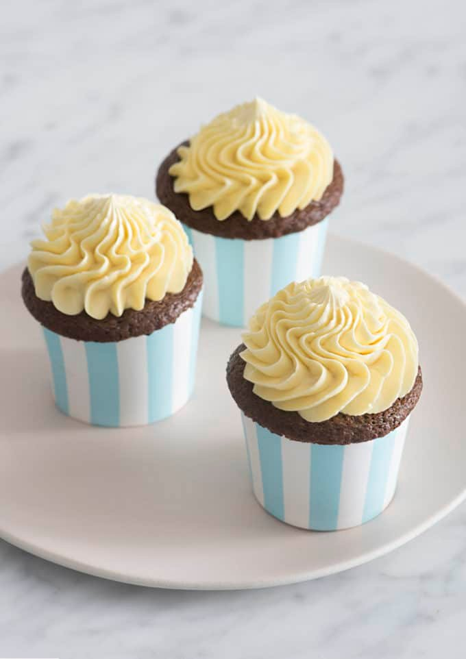 A photo of three chocolate cupcakes topped with dollops of french buttercream.